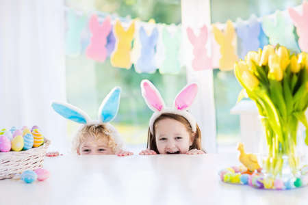 Boy and girl in bunny ears at breakfast on Easter morning at table with Easter eggs basket. Kids celebrating Easter. Children on Easter egg hunt. Home decoration - pastel bunny banner and flowers.