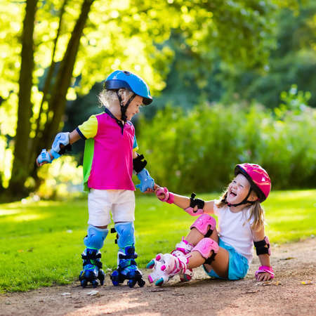 roller: Girl and boy learn to roller skate in summer park. Children wearing protection pads and safety helmet for safe roller skating ride. Active outdoor sport for kids. Siblings help and support each other