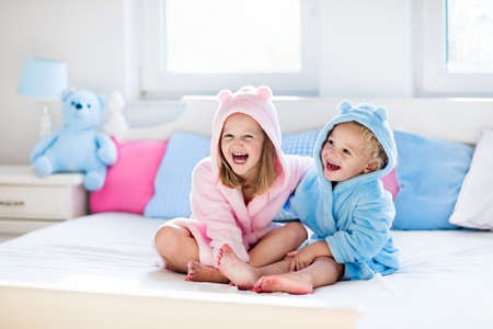 Happy laughing kids, boy and girl in soft bathrobe after bath play on white bed with blue and pink pillows in sunny bedroom. Child in clean and dry towel. Wash, infant hygiene, health and skin care.