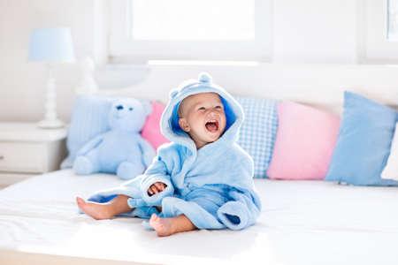 Mignon heureux rire bébé en peignoir doux après lecture de bain sur lit blanc avec des oreillers bleu et rose sous le soleil de la chambre des enfants. Enfant dans une serviette propre et sèche. Laver, l'hygiène infantile, la santé et les soins de la peau. Banque d'images - 70451272