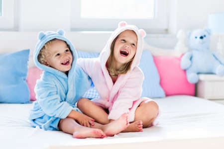 Happy laughing kids, boy and girl in soft bathrobe after bath play on white bed with blue and pink pillows in sunny bedroom. Child in clean and dry towel. Wash, infant hygiene, health and skin care. Stock Photo - 70451280