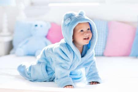 Cute glücklich lachend Baby im weichen Bademantel nach Bad Spiel auf weißem Bett mit blauen und rosa Kissen im sonnigen Kinderzimmer. Kind in einem sauberen und trockenen Tuch. Waschen, Säuglingspflege, Gesundheit und Hautpflege.