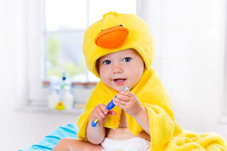 after bath: Little baby in yellow duck towel brushing teeth on changing table after bath. Infant boy with tooth brush. Dental hygiene, toothbrush and toothpaste for young kids. Child teeth and oral health care. Stock Photo