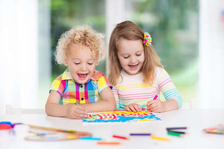 niÑos con libros: Little boy and girl draw together in white room with window. Kids doing homework, painting and drawing. Children paint with paintbrush color and pencils. Art and crafts for toddler and preschooler. Foto de archivo