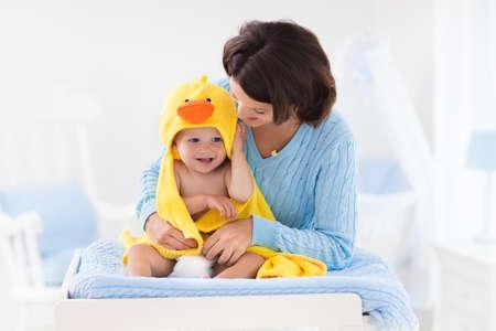 Moeder en baby verandering luier na bad in wit kwekerij. Weinig jongen in gele eend badcape op commode in schone, droge luier. Moeder de verzorging van baby kind. Kids kamer interieur en hygiëne. Stockfoto