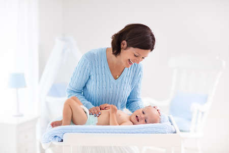 diaper changing table: Mother and baby change diaper after bath in white nursery with bed and rocking chair. Little boy on changing table in clean dry nappy. Mom taking care of infant child. Kids room interior and hygiene.