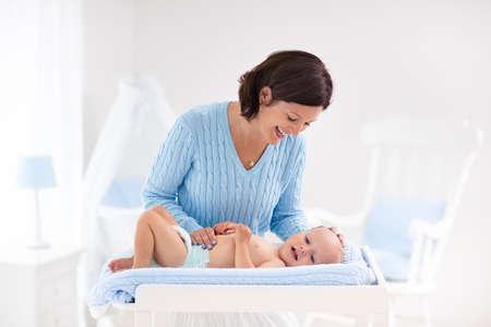 Mutter und Baby ändern Windel nach dem Bad in weiß Kinderzimmer mit Bett und Schaukelstuhl. Kleiner Junge auf dem Tisch in sauberen, trockenen Windel wechseln. Mama kümmert sich um Kind Kind. Kinderzimmer Interieur und Hygiene.