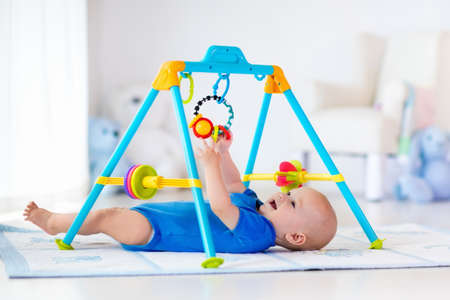 kids toys: Cute baby boy on colorful playmat and gym, playing with hanging rattle toys. Kids activity and play center for early infant development. Newborn child kicking and grabbing toy in white sunny nursery