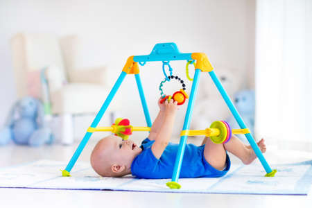 playmat: Cute baby boy on colorful playmat and gym, playing with hanging rattle toys. Kids activity and play center for early infant development. Newborn child kicking and grabbing toy in white sunny nursery