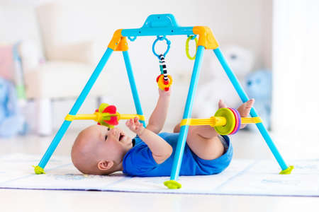 entertainment center: Cute baby boy on colorful playmat and gym, playing with hanging rattle toys. Kids activity and play center for early infant development. Newborn child kicking and grabbing toy in white sunny nursery