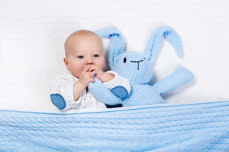 knitted jacket: Funny little baby wearing a warm knitted jacket playing with toy bunny relaxing on white cable knit blanket in sunny nursery. Kids winter clothing and bedding. Hand made toys and textile for children. Stock Photo