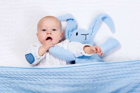 baby toys: Funny little baby wearing a warm knitted jacket playing with toy bunny relaxing on white cable knit blanket in sunny nursery. Kids winter clothing and bedding. Hand made toys and textile for children. Stock Photo