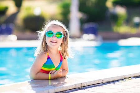 petite fille maillot de bain: Petite fille jouant dans la piscine extérieure sauter dans l'eau sur les vacances d'été sur l'île tropicale de plage. Enfant apprendre à nager dans la piscine extérieure du complexe hôtelier de luxe. jouet de l'eau et des lunettes de soleil pour les enfants. Banque d'images