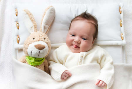 knitted jacket: Newborn little baby wearing a warm knitted jacket playing with toy bunny relaxing on white cable knit blanket in sunny nursery. Kids winter clothing and bedding. Hand made toys and textile for children.
