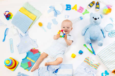 Baby on white background with clothing, toiletries, toys and health care accessories. Wish list or shopping overview for pregnancy and baby shower. View from above. Child feeding, changing and bathing 스톡 콘텐츠