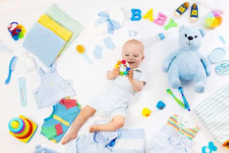 Bebé sobre fondo blanco con ropa, artículos de tocador, juguetes y accesorios para el cuidado de la salud. Lista de deseos o resumen de compras para el embarazo y el baby shower. Vista desde arriba. Alimentación infantil, cambio y baño