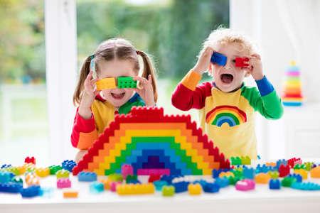 Niño jugando con juguetes de colores. Niña y divertida bebé rizado con bloques de juguete educativos. Los niños juegan en la guardería o al preescolar. Desorden en la habitación de los niños. Los niños pequeños a construir una torre en el jardín de infantes. Centrarse en la niña. Foto de archivo