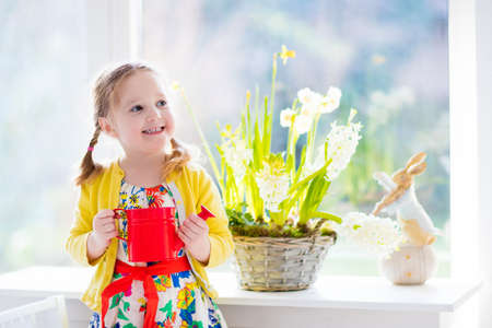 home and garden: Cute girl watering first spring flowers. Easter home interior and decoration. Child taking care of plants. Kid with water can. Toddler with toy bunny. Little gardener with hyacinths and daffodils. Stock Photo
