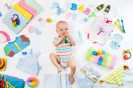 stuff toy: Baby on white background with clothing, toiletries, toys and health care accessories. Wish list or shopping overview for pregnancy and baby shower. View from above. Child feeding, changing and bathing Stock Photo