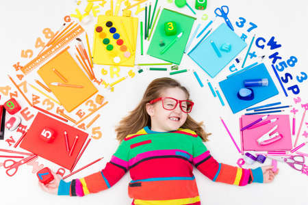 Little girl with school supplies, books, drawing and painting tools and materials. Happy back to school student. Art and crafts for kids. Child learning rainbow colors, alphabet letters and numbers.