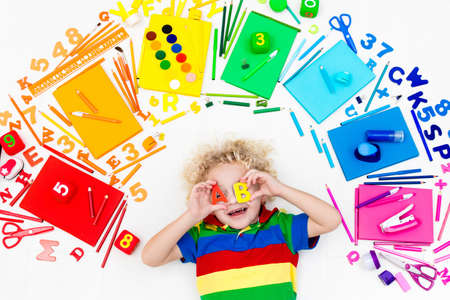 niño parado: Little boy with school supplies, books, drawing and painting tools and materials. Happy back to school student. Art and crafts for kids. Child learning rainbow colors, alphabet letters and numbers.