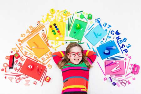 Niña con útiles escolares, libros, dibujo y herramientas de pintura y materiales. Feliz de nuevo a los estudiantes de la escuela. Arte y manualidades para niños. Niño que aprende colores del arco iris, letras del alfabeto y números. Foto de archivo