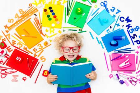 Little boy with school supplies, books, drawing and painting tools and materials. Happy back to school student. Art and crafts for kids. Child learning rainbow colors, alphabet letters and numbers.
