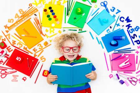 niño parado: Niño con útiles escolares, libros, herramientas y materiales de dibujo y pintura. Feliz de nuevo a la escuela. Arte y manualidades para niños. Niño que aprende colores del arco iris, letras del alfabeto y números.