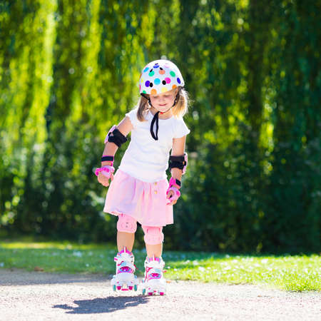 elbow pad: Little girl learning to roller skate in sunny summer park. Child wearing protection ? elbow and knee pads, wrist guards and safety helmet for safe roller skating ride. Active outdoor sport for kids.