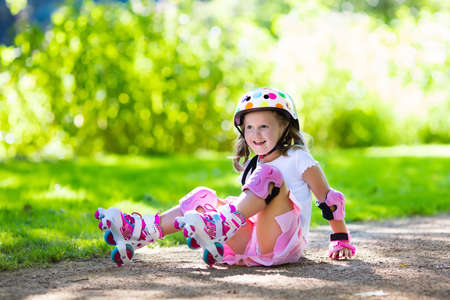 skate park: Little girl learning to roller skate in sunny summer park. Child wearing protection elbow and knee pads, wrist guards and safety helmet for safe roller skating ride. Active outdoor sport for kids. Stock Photo