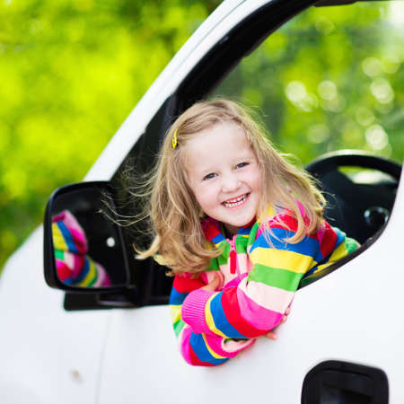 夏の日の家族での休暇の遠征で休憩中にフロントの運転席に座って車の窓から見ている面白いおさげの少女。白のミニバンの子。子供たちと車で旅