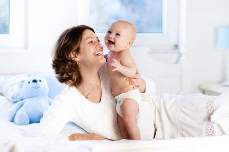 母と子白いベッドの上。日当たりの良い寝室で遊んでおむつでママと赤ちゃんの男の子。親と子供の家でのんびり。家族で一緒に楽しんで。ベッド