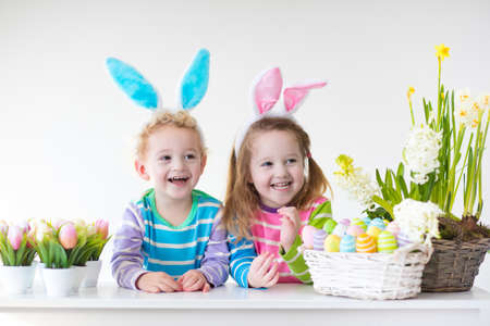 flower art: Happy children celebrate Easter at home. Boy and girl wearing bunny ears enjoying egg hunt. Kids playing with color eggs and flower basket. Spring crafts and art for toddler child and preschooler kid. Stock Photo