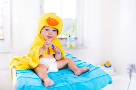 Little baby in yellow duck towel brushing teeth on changing table after bath. Infant boy with tooth brush. Dental hygiene, toothbrush and toothpaste for young kids. Child teeth and oral health care. Stock Photo