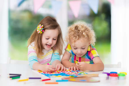 Little boy and girl draw together in white room with window. Kids doing homework, painting and drawing. Children paint with paintbrush color and pencils. Art and crafts for toddler and preschooler. Stock Photo