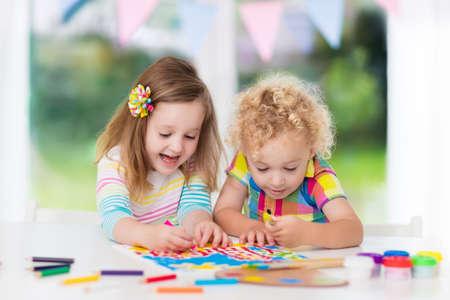 Niño y niña dibujan juntos en la sala blanca con ventana. Niños haciendo la tarea, la pintura y el dibujo. Los niños pintan con el color de la brocha y lápices. Arte y manualidades para el niño y el niño en edad preescolar. Foto de archivo - 71505465