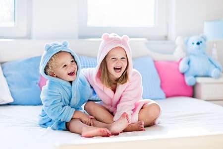 Gelukkige lachende jonge geitjes, jongen en meisje in zachte badjas na badspel op wit bed met blauwe en roze hoofdkussens in zonnige slaapkamer. Kind in schone en droge handdoek. Wassen, babyhygiëne, gezondheid en huidverzorging. Stockfoto