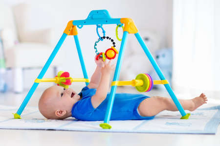 teether: Cute baby boy on colorful playmat and gym, playing with hanging rattle toys. Kids activity and play center for early infant development. Newborn child kicking and grabbing toy in white sunny nursery