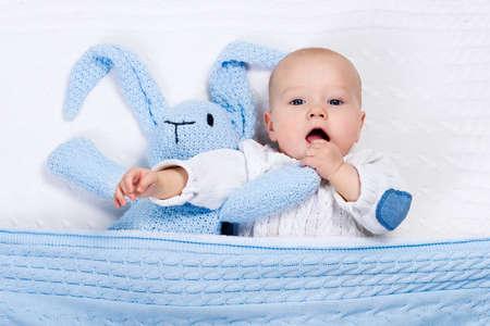 Petit bébé drôle portant un jeu chaude veste tricotée avec le jouet lapin détente sur câble blanc couverture tricoter en pépinière ensoleillée. Enfants textiles pour l'hiver et la literie. Hand made jouets et textiles pour les enfants.