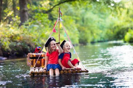 해적 의상과 보물 상자, spyglasses와 모자를 입고 아이, 그리고 뜨거운 여름 날에 강에 나무 뗏목 항해에서 재생 칼입니다. 어린이를위한 해적 역할 게임. 가족을위한 물 재미.