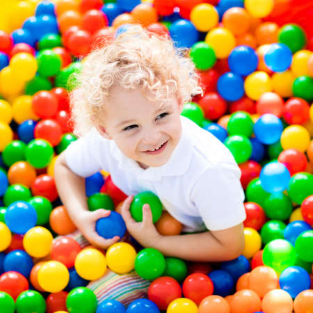 arcades: Happy laughing boy having fun in ball pit on birthday party in kids amusement park and indoor play center. Child playing with colorful balls in playground ball pool. Activity toys for little kid.