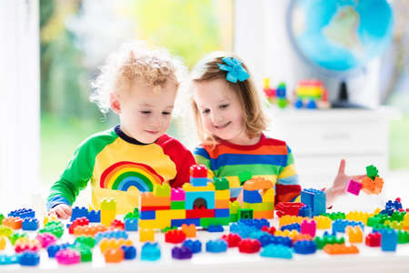 baby toys: Child playing with colorful toys. Little girl and funny curly baby boy with educational toy blocks. Children play at day care or preschool. Mess in kids room. Toddlers build a tower in kindergarten. Stock Photo