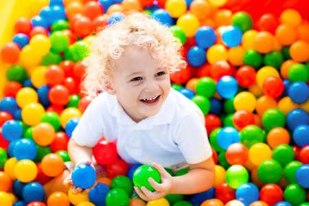 子供遊園地、屋内のプレイ センターで誕生日パーティーにボールをピットで楽しんで幸せな笑い少年。カラフルなボールが遊び場のボールプールで
