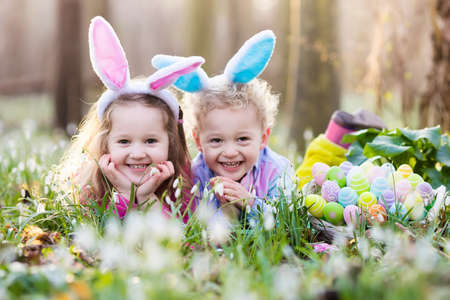 Kids on Easter egg hunt in blooming spring garden. Children with bunny ears searching for colorful eggs in snow drop flower meadow. Toddler boy and preschooler girl in rabbit costume play outdoors. Imagens - 72028582