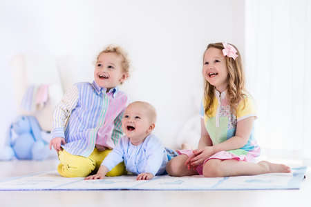 Group of three kids playing in a white bedroom. Children play at home. Preschooler girl, toddler boy and baby in nursery. Happy little brothers and sister bonding having fun together. Siblings love.