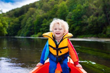 viaje familia: niño feliz disfrutando de paseo en kayak en el hermoso río. Poco kayak rizado muchacho del niño en el día caluroso de verano. Actividad en el mar y la diversión de camping. Canoa para los niños. Niño divertido con la embarcación en un barco. Foto de archivo