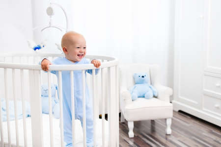Funny little baby standing in round modern bed with mobile in white nursery with window. Infant boy in blue pajamas with teddy bear toy. Nursery interior for young child. Kids sleep wear and bedding.