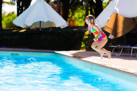 Gelukkig meisje met opblaasbare speelgoedring die in openlucht zwembad in een tropische toevlucht tijdens de vakantie van de familiezomer springt. Kinderen leren zwemmen. Waterplezier voor kinderen.