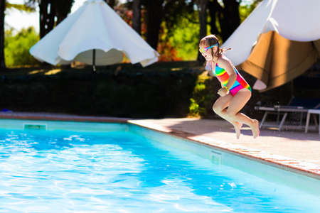 Happy little girl with inflatable toy ring jumping into outdoor swimming pool in a tropical resort during family summer vacation. Kids learning to swim. Water fun for children. Фото со стока