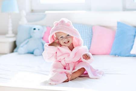Lindo bebé que ríe feliz en bata de baño suave después del baño de juego en la cama blanca con almohadas azules y rosas en la habitación de los niños soleado. Niño en una toalla limpia y seca. Lavado, higiene infantil, la salud y el cuidado de la piel. Foto de archivo